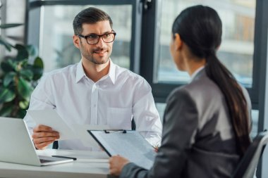 handsome male translator holding documents on meeting with businesswoman