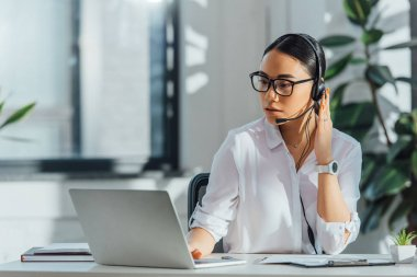 asian translator working online with headset and laptop in office
