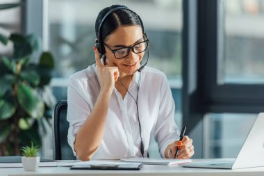 smiling asian translator working online with headset and laptop in office