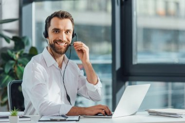 cheerful male translator in eyeglasses working online with headset and laptop
