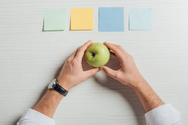cropped view of businessman holding apple on table with empty note stickers