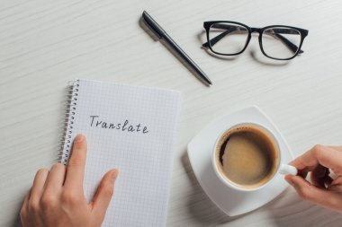 cropped view of translator with notepad, pen, eyeglasses and cup of coffee