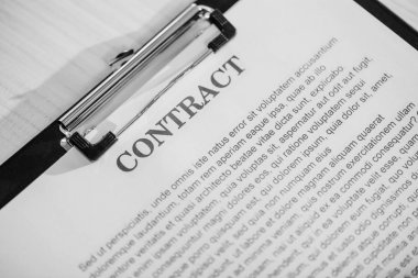 close up of business contract on clipboard on white table