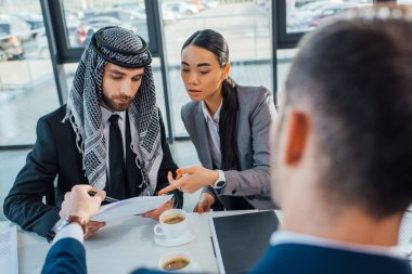 multicultural business partners discussing contract on meeting with translator in office