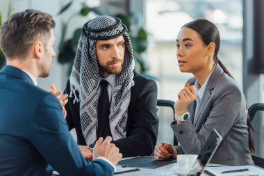 multicultural business partners talking on meeting with translator in office