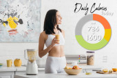 Fotografie Atraktivní fit sportovkyně se usmívá a drží sklenici smoothie v blízkosti měřicí pásky na kuchyňském stole s denní kalorií ilustrace