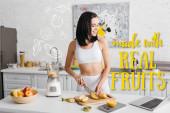 Lächelnde Sportlerin blickt auf Laptop, während sie Obst in der Nähe des Mixers auf dem Küchentisch schneidet, hergestellt mit echten Früchten Illustration