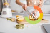 Selektivní zaměření měřicí pásky a váhy v blízkosti fit dívka řezání čerstvého ovoce pro smoothie na kuchyňském stole, denní kalorie ilustrace
