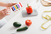Cropped view of girl holding smartphone with daily diet plan app near vegetables, scales and measuring tape on kitchen table