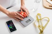 Fotografie oříznutý pohled ženy, jak dává rajčata na váhy v blízkosti smartphonu s aplikací počítání kalorií a měřicí páskou na kuchyňském stole