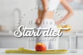 Fotografie Selektivní zaměření jablek, měřicí páska a sklenice vody v blízkosti fit sportovkyně v kuchyni, začít dietní ilustrace