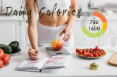 Ausgeschnittene Ansicht einer fitten Sportlerin, die Kalorien schreibt, während sie Apfel auf dem Küchentisch wiegt, tägliche Kalorien Illustration
