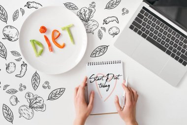 Top view of woman holding pen and notebook with start diet today words near lettering diet from vegetable slices on plate and laptop on white background with vegetables and leaves illustration