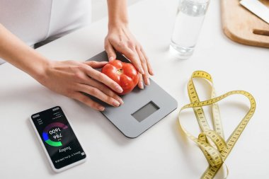 cropped view of woman putting tomato on scales near smartphone with calorie counting app and measuring tape on kitchen table