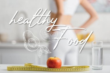Selective focus of apple, measuring tape and glass of water near fit sportswoman in kitchen, healthy food illustration