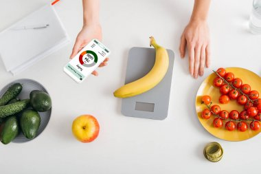 Top view of girl holding smartphone with calorie counting app while weighing banana on kitchen table near fresh vegetables