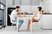 Side view of sensual woman in bra and shirt flirting with boyfriend during breakfast in kitchen