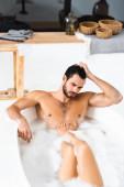Svalnatý muž dívá pryč při koupeli s přítelkyní doma