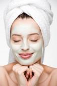 lächelndes Mädchen mit nährender Gesichtsmaske und Handtuch auf dem Kopf, die Hände in der Nähe des Gesichts isoliert auf weißem Grund