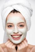 glückliches Mädchen mit nährender Gesichtsmaske und Handtuch auf dem Kopf, das isoliert auf weiß in die Kamera schaut