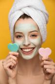 fröhliches Mädchen mit nährender Maske im Gesicht, die herzförmige Kosmetikschwämme hält, die auf gelb isoliert sind