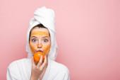 Fotografie aufgeregtes Mädchen mit Zitrusgesichtsmaske, die Mandarine in Mundnähe hält, isoliert auf rosa