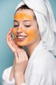 fröhliches Mädchen mit zitrusfarbener Gesichtsmaske, die Gesicht isoliert auf blau berührt