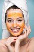 Fotografie glückliches Mädchen mit zitrusfarbener Gesichtsmaske, das die Hände vor dem Gesicht hält und in die Kamera schaut