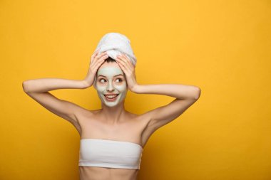 happy girl with nourishing facial mask and towel on head looking away on yellow background