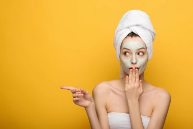 shocked girl with nourishing facial mask and towel on head covering mouth with hand and pointing with finger on yellow background