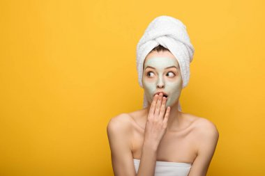 shocked girl with nourishing facial mask covering mouth with hand and looking away isolated on yellow