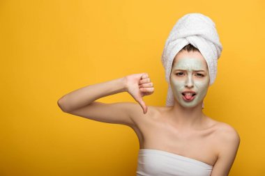 displeased girl with nourishing facial mask showing thumb down and sticking out tongue up on yellow background