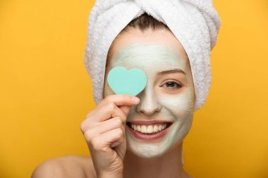 happy girl with nourishing mask on face covering eyes with heart-shaped cosmetic sponge on yellow background