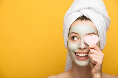 cheerful girl with nourishing facial mask covering eye with heart-shaped cosmetic sponge on yellow background