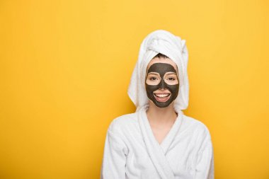 smiling girl with facial clay mask and towel on head looking at camera on yellow background