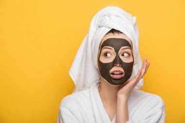 surprised girl with facial clay mask and towel on head holding hand near face isolated on yellow