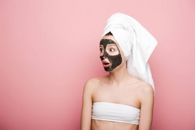 shocked girl with facial clay mask looking away while standing with open mouth on pink background
