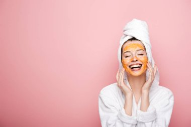 happy girl with citrus facial mask touching face with closed eyes isolated on pink