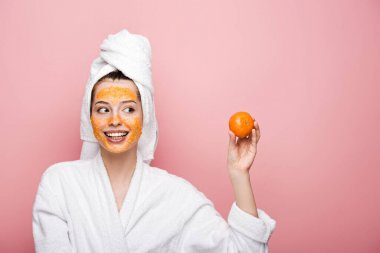 happy girl with citrus facial mask looking at tangerine isolated on pink