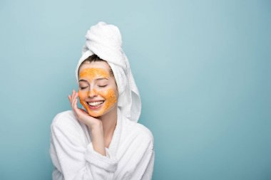 happy girl with citrus facial mask touching face with closed eyes isolated on blue