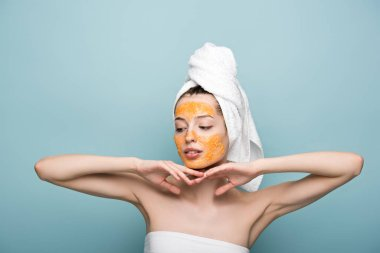 pensive girl with citrus facial mask holding hands near face on blue background