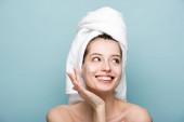 šťastný atraktivní dívka použití hydratační obličejová maska při pohledu pryč izolované na modré
