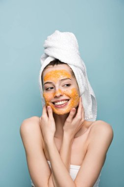 cheerful girl with citrus facial mask looking away and touching face isolated on blue