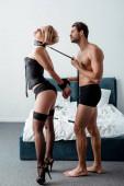 dominanter Mann hält bdsm Leine und berührt Seil an gefesselten Händen der unterwürfigen Frau