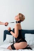 Mann hält BDSM-Leine an unterwürfiger Frau, die auf Bett sitzt