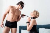 Seitenansicht eines Mannes mit Augenmaske, der eine unterwürfige Frau mit betenden Händen an der Leine hält