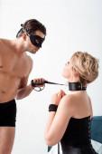 Mann mit Augenmaske hält bdsm Leine und schaut unterwürfige Frau an