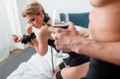 Selektiver Fokus der verführerischen Frau in der Nähe des dominanten Mannes mit einem Glas Rotwein
