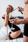 Selektiver Fokus des dominanten Mannes mit einem Glas Rotwein, der die unterwürfige Frau an der Leine hält