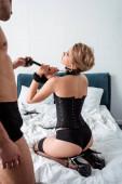 Selektiver Fokus des Mannes, der eine Leine an einer leidenschaftlichen Frau im Schlafzimmer hält
